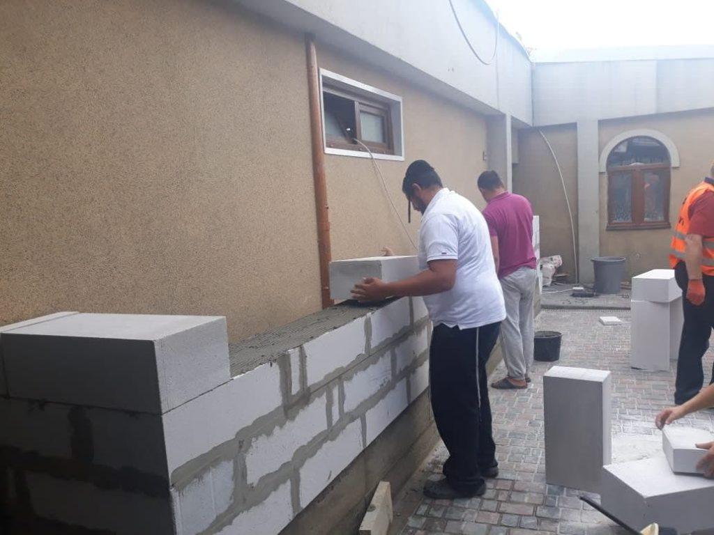 בניית קיר סמוך לכניסה לעזרת נשים בציון רבי נחמן מברסלב באומן